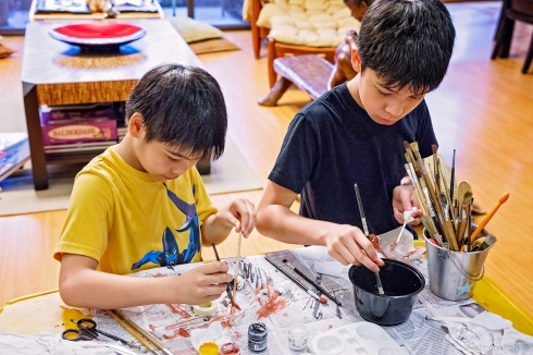 Creating their own Harry Potter wands out of chopsticks and paint